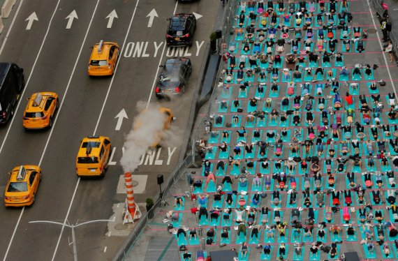 People participate in a yoga class during an annual Solstice event in the Times Square district of New York